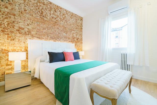 dormitor cu perete de caramida expusa