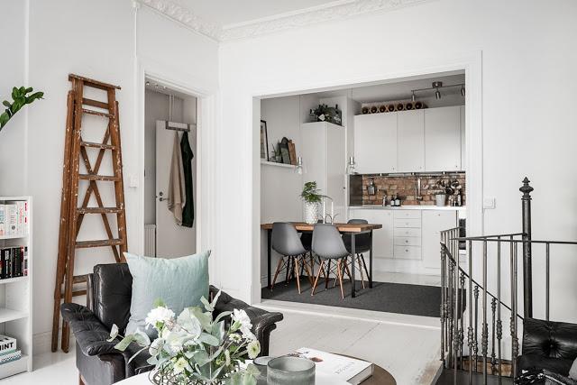 Dormitorul la nivelul inferior și bucătăria la etaj într-o mansardă pe două niveluri din Suedia