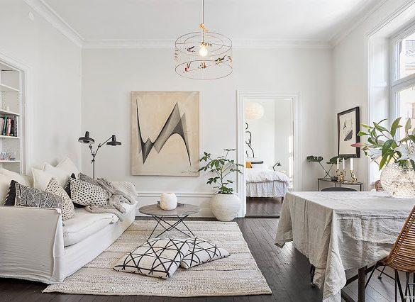 Amenajare în tonuri neutre de culoare, bucătărie neagră și motive grafice într-un apartament de 61 m²