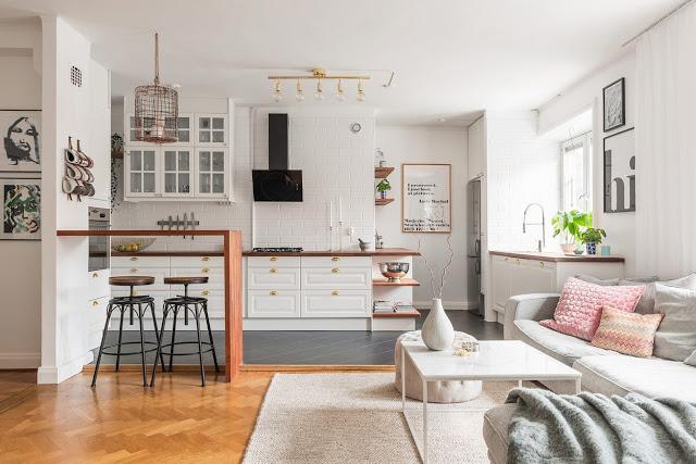 Bucătărie deschisă către living și accente pastelate de culoare într-un apartament
