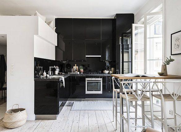 Bucătărie neagră și pat deasupra intrării într-o garsonieră de 37 m²