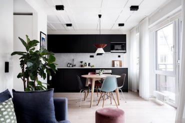 ucătărie neagră și perete de sticlă între dormitor și living într-un apartament de 48 m²