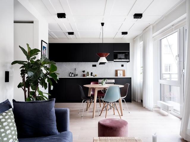 Bucătărie neagră și perete de sticlă între dormitor și living într-un apartament de 48 m²