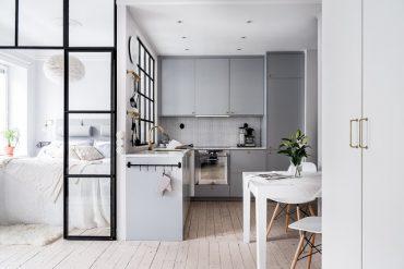 Gri, accente aurii și dormitor amenajat lângă bucătărie într-o garsonieră de 37 m²