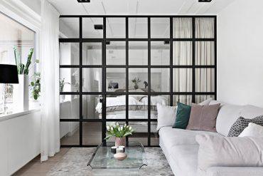 Perete de sticlă între dormitor și living într-un apartament de 49 m² din Suedia